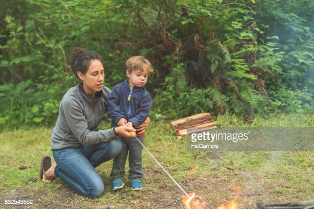 Beautiful young ethnic mom helps her son roast a s'more over the campfire