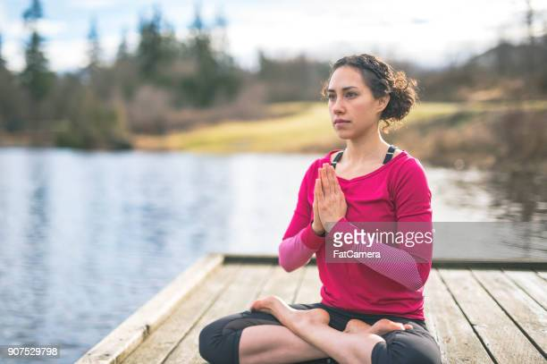 A Beautiful Young Eurasian Woman Practices Yoga By a Lake