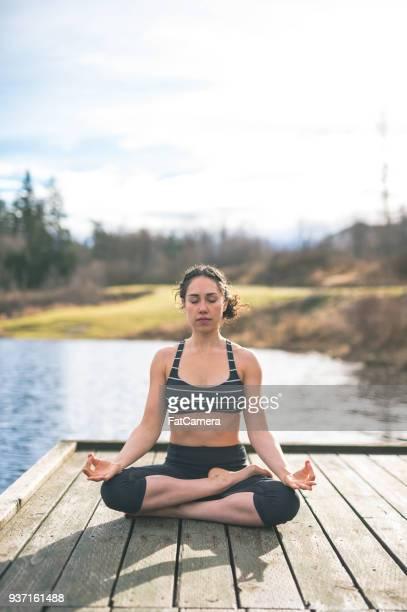 Eine schöne junge eurasische Frau praktiziert Yoga am See