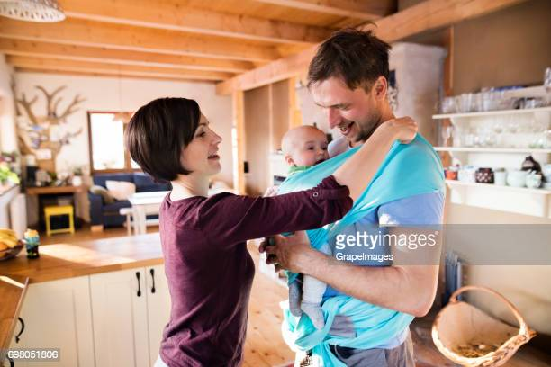 Beautiful young family with cute little son at home in the kitching, mother helping father to put baby into the sling
