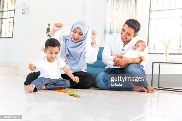 beautiful young family with spending time in house - islam stock pictures, royalty-free photos & images