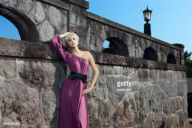 beautiful young fashion model in purple gown at rock wall - purple dress stock pictures, royalty-free photos & images