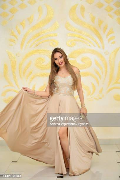 beautiful young fashion model standing against wall - gold dress stock pictures, royalty-free photos & images
