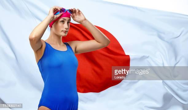 日本国旗の前でポーズをとる美しい若い女性アスリート - オリンピック選手 ストックフォトと画像