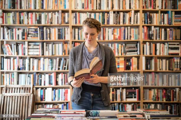 beautiful young female customer reading book at bookstore - reading stock pictures, royalty-free photos & images