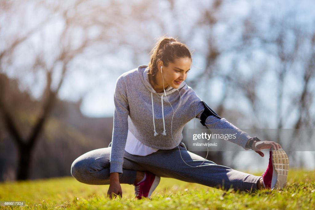 Beautiful young female doing exercises in nature : Stock Photo