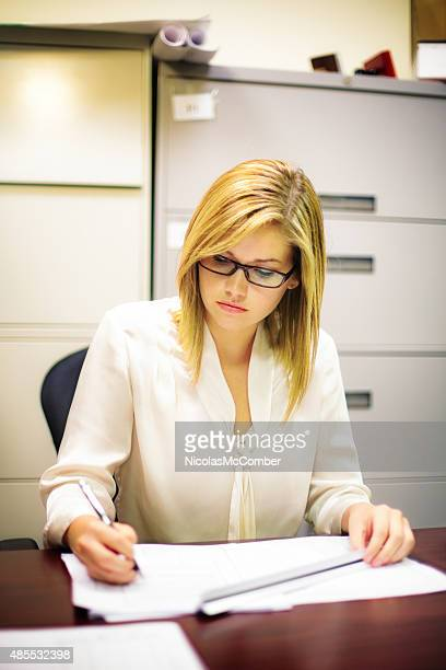 Beautiful young female engineer working on project with ruler vertical