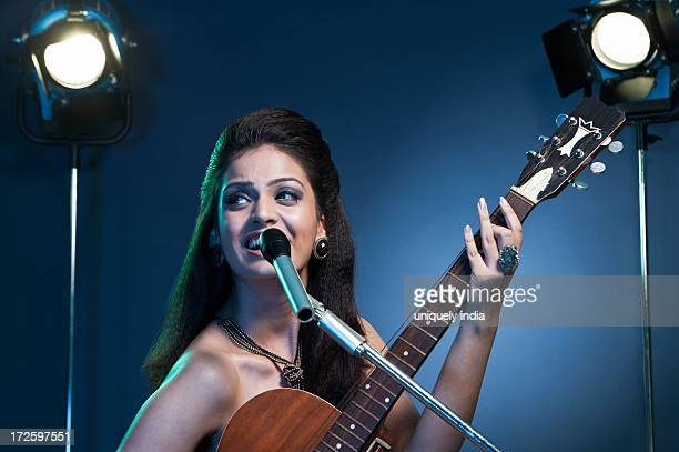Beautiful young female singer performing with guitar on stage
