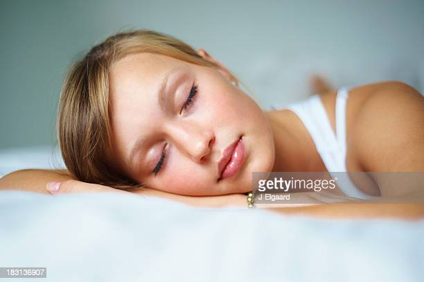 Beautiful young female sleeping on bed