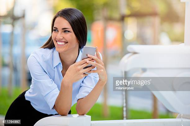 Beautiful young female smiiling and holding smartphone