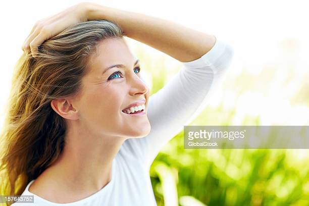 Beautiful young female smiling with hand in hair