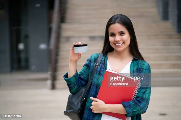 beautiful young female student holding a card to edit and notebooks at the college campus - identity card stock pictures, royalty-free photos & images