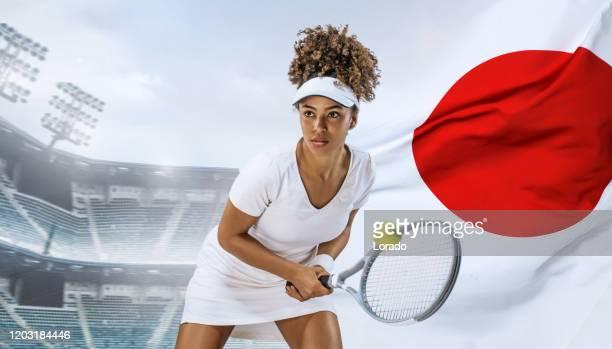 日本国旗を掲げた架空のスタジアムで美しい若手テニス選手 - オリンピック選手 ストックフォトと画像