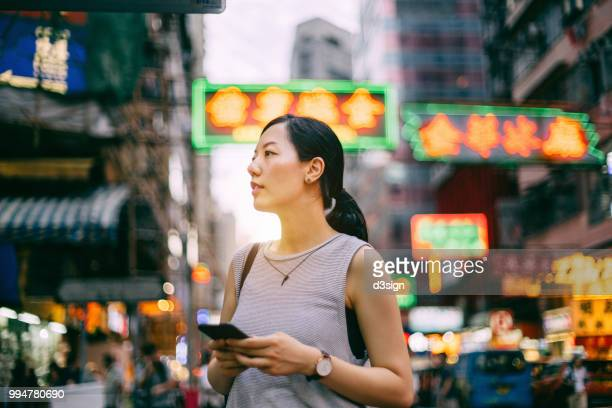 beautiful young female traveller searching for direction on smartphone on busy city street, against colourful neon commercial sign and city buildings - asia map stock pictures, royalty-free photos & images