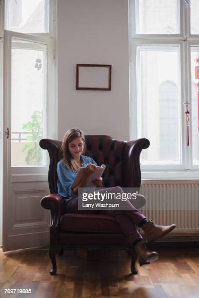 Beautiful young female university student sitting on armchair while reading book at home