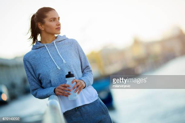 Femme belle jeune fitness vous pause après le runnig