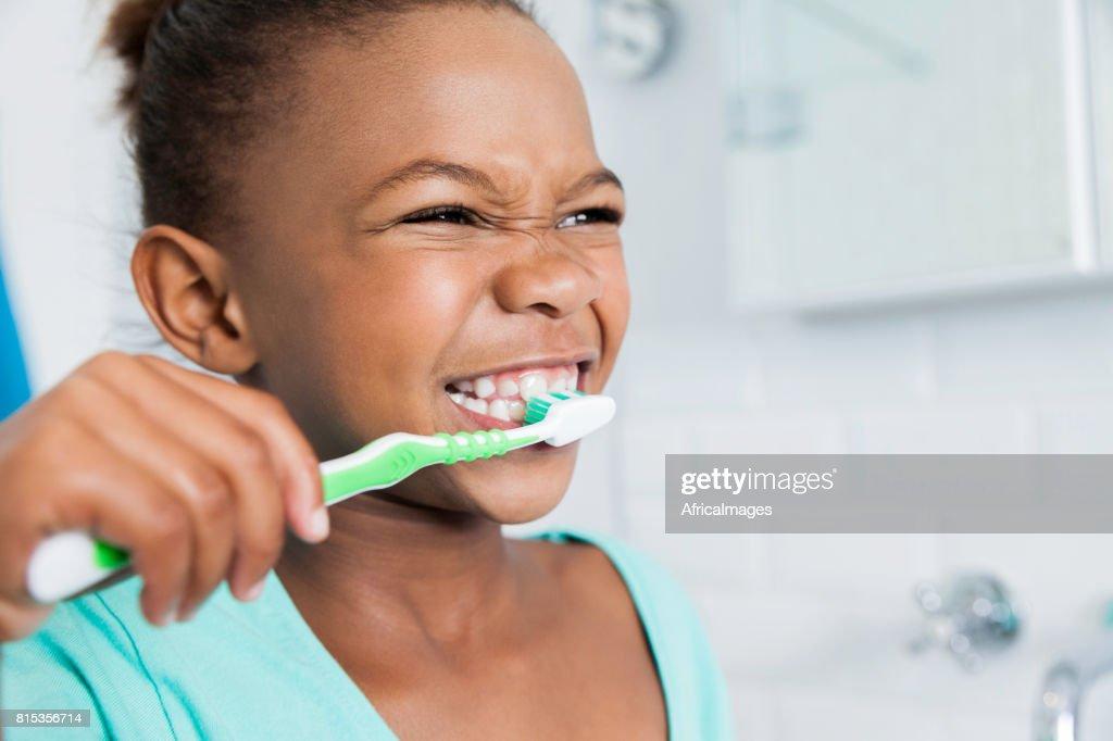 Beautiful young girl brushing her teeth. : Stock Photo