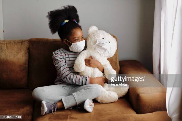 beautiful young girl holding teddy bear on couch - stress coronavirus stock pictures, royalty-free photos & images