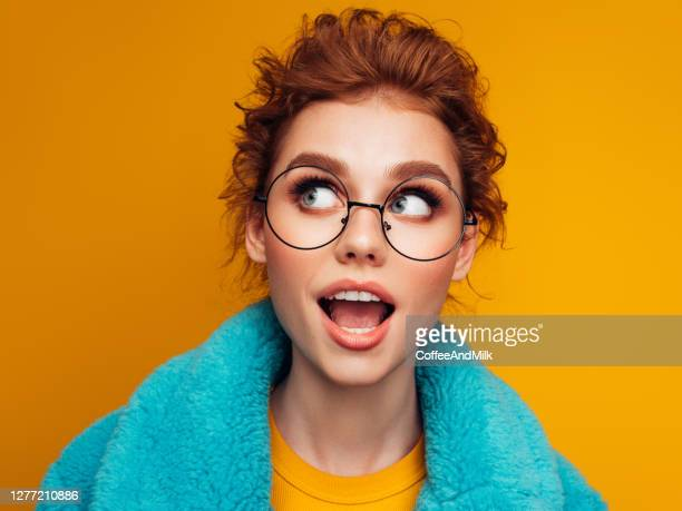 beautiful young girl in turquoise fur coat on a blue background - coat stock pictures, royalty-free photos & images