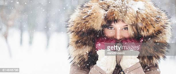 Jovem linda ao ar livre na neve com capuz