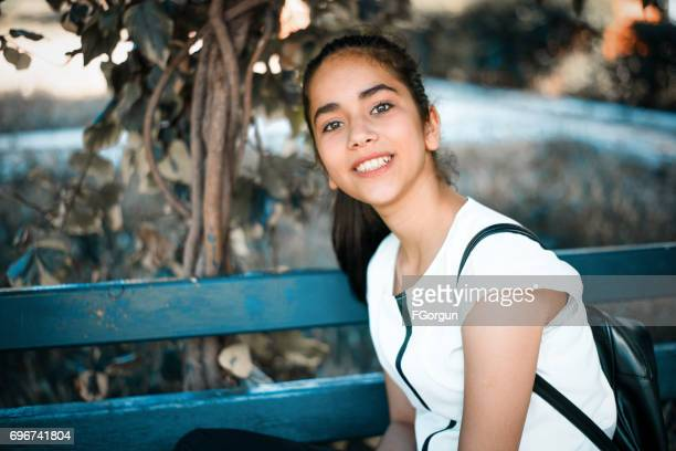 Beautiful young girl sitting on a bench in park