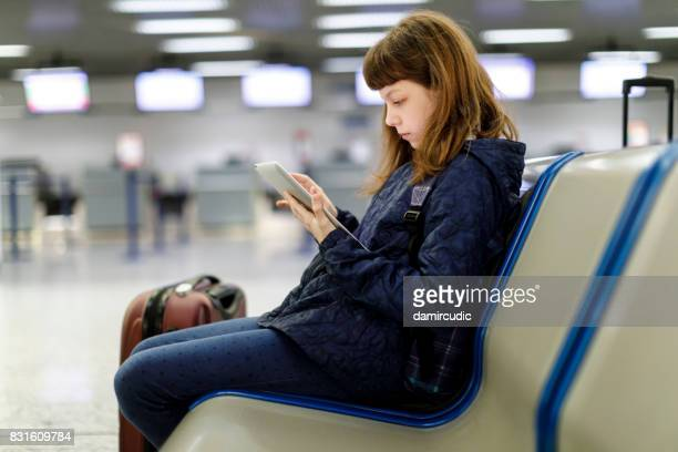 Beautiful young girl using her digital tablet at the airport
