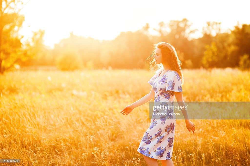 Beautiful young girl walking flower park sunset background Soft focus : Stock Photo