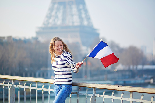 Beautiful young girl with French national flag 535524614