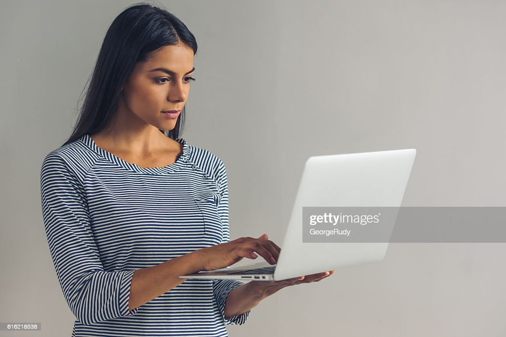 Beautiful young girl with gadget : Stock Photo