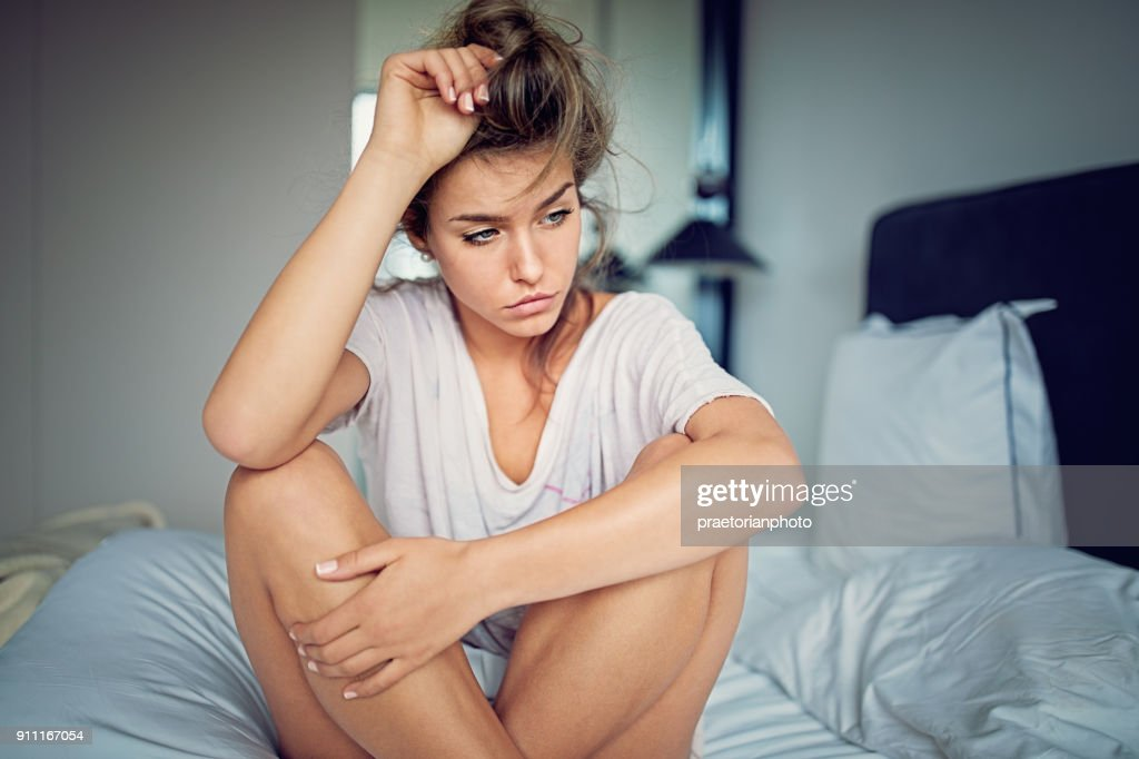 立ちベッドで悲しい関係の難しさを持つ美しい少女 : ストックフォト