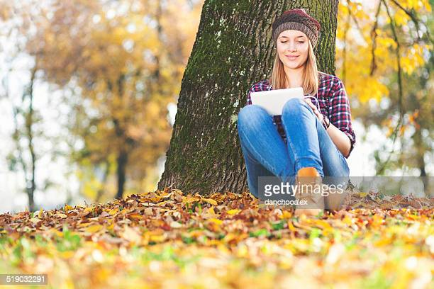 Beautiful young girl with tablet PC enjoying autumn