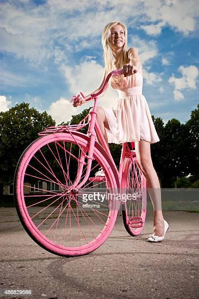 Belle jeune femme avec vélo vintage rose couleur peint