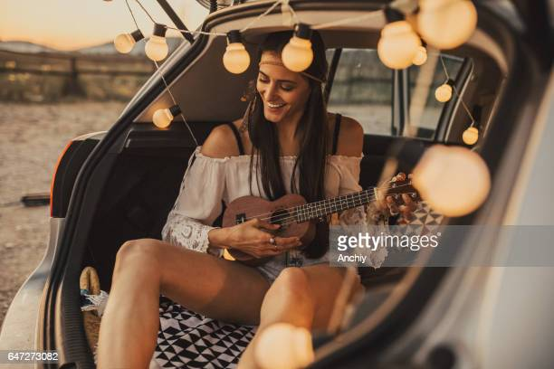 Beautiful young hipster or hippie woman playing ukulele.