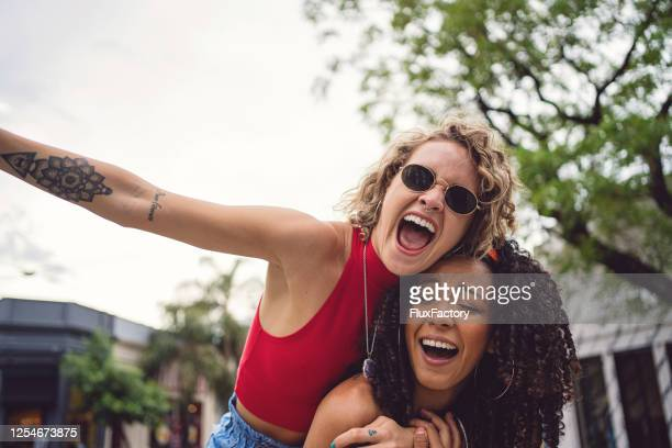 beautiful young hispanic female friends having fun outdoors - ecstatic stock pictures, royalty-free photos & images