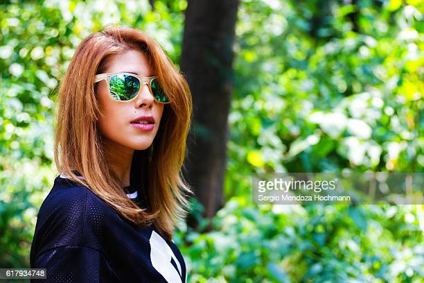 Beautiful young Hispanic woman looking at camera with sunglasses on