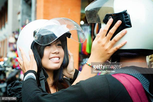 Beautiful young Indonesian couple placing each other's helmets