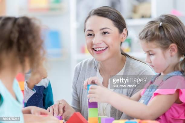 schöne junge kindergärtnerin sitzt mit schülern in der schule - preschool stock-fotos und bilder