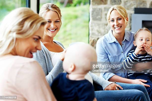 Beautiful young ladies with their kids sitting together