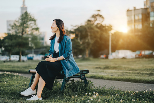 Beautiful young lady enjoys the quiet time in park during sunset - gettyimageskorea