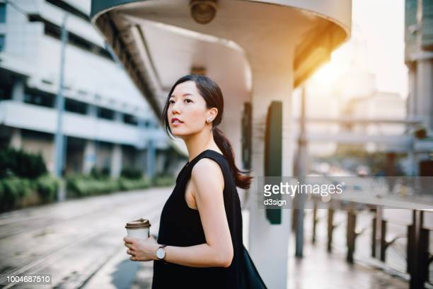 beautiful young lady holding coffee cup waiting for tram at station in city - rush hour stock pictures, royalty-free photos & images