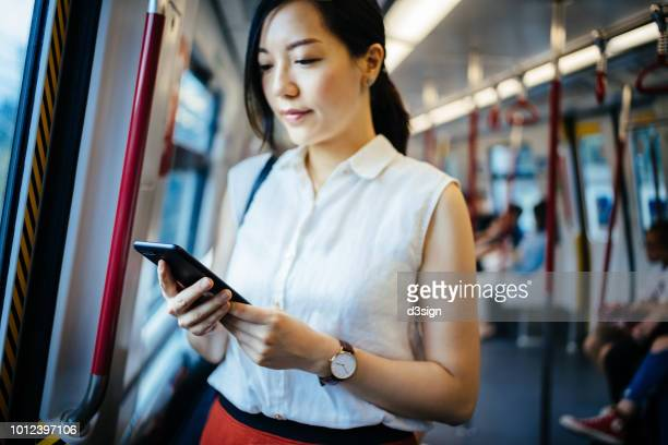 beautiful young lady text messaging on smartphone while riding on subway mtr train - 鉄道 ストックフォトと画像