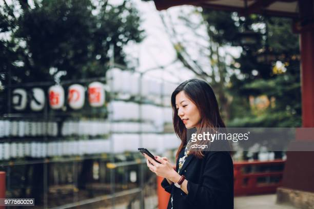 Beautiful young lady using smartphone outdoors against traditional Japanese house in town
