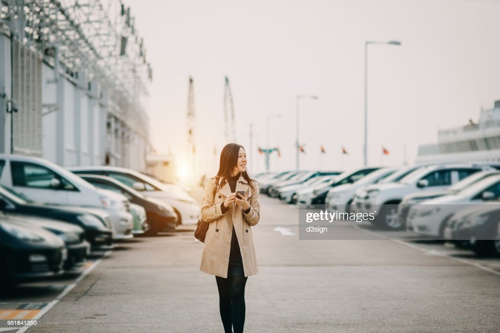 Beautiful young lady using smartphone while walking to car in rooftop carpark in city : ストックフォト