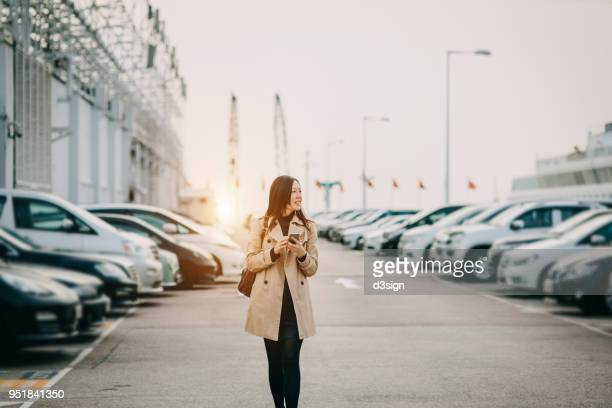 beautiful young lady using smartphone while walking to car in rooftop carpark in city - car park stock pictures, royalty-free photos & images