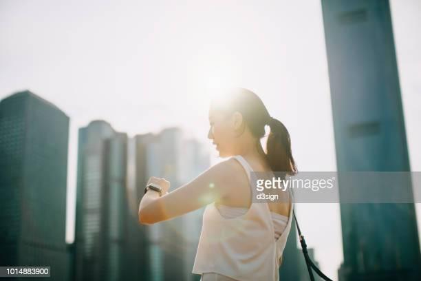 beautiful young lady using smartwatch against urban cityscape under sun flare - ver a hora - fotografias e filmes do acervo