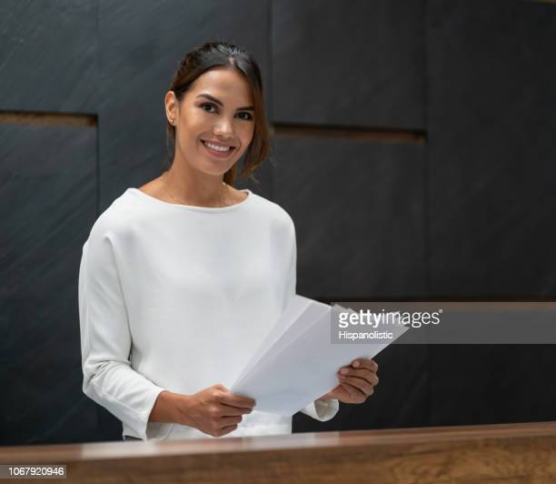 Beautiful young latin american business woman working at the office looking at camera smiling