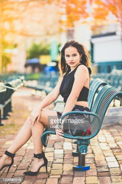 beautiful young latina model on a park bench posing - mini skirt stock pictures, royalty-free photos & images