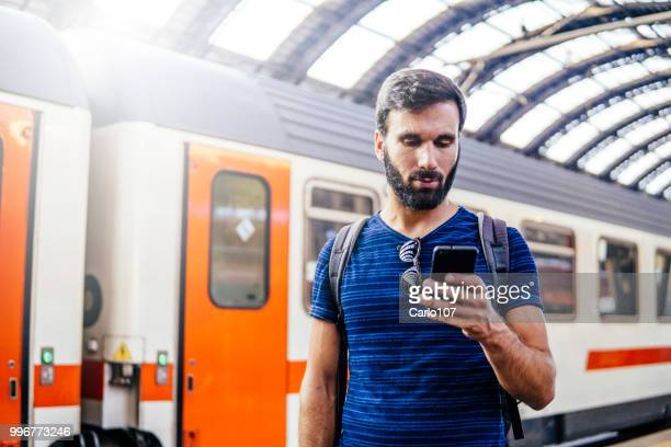 Beautiful young man looking at the phone while waiting for the train