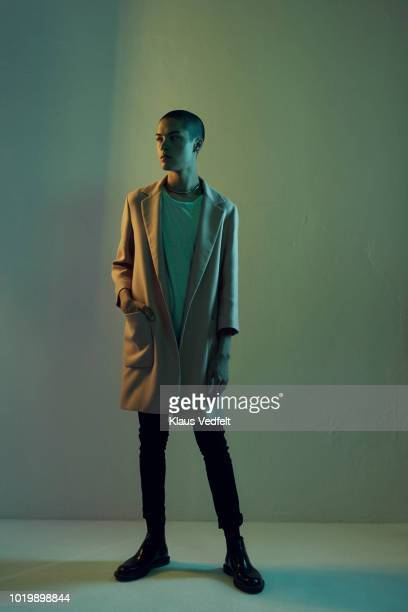 beautiful young man looking out, shot on studio - green coat stock pictures, royalty-free photos & images