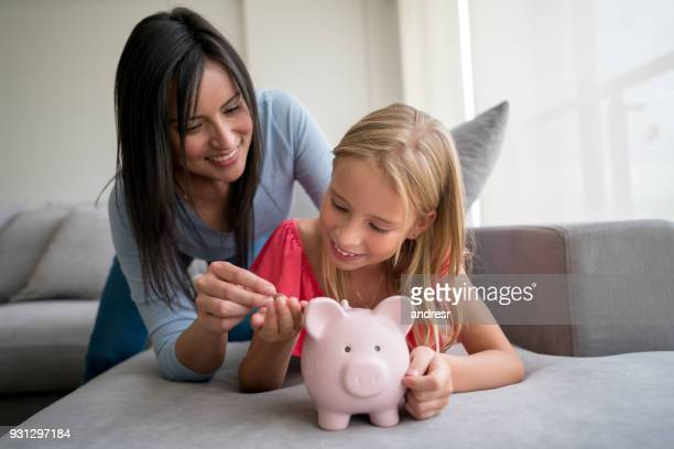 beautiful young mom giving coins to her daughter so she can put them in the pink piggy bank - piggy bank stock pictures, royalty-free photos & images